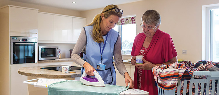 A caregiver is helping an older lady with ironing